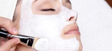 Cosmetician applying facial beauty mask for young beautiful woman at spa salon