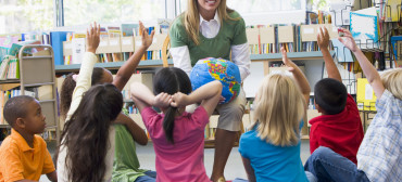 Kindergarten teacher and children with hands raise